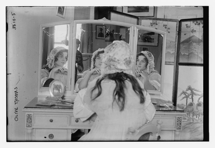 Olive_Thomas_in_April_1916_looking_into_a_mirror_with_a_glimpse_of_the_photographer